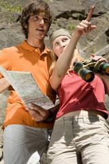 Junges Paar mit Karte und Fernglas, Frau zeigt etwas