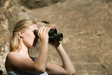 Junge Frau auf der Suche durch Fernglas