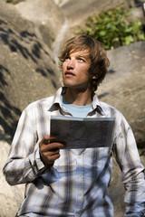 Junger Mann mit Karte in den Bergen