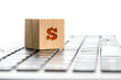 Online earnings concept with a wooden block with dollar sign