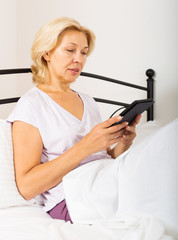 mature woman with eBook laying in  bed