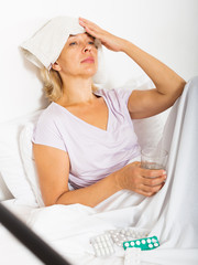Senior lady with pills and towel compress