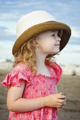 Little girl standing on the beach wearig big hat