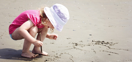 Little girl drawing in the sand on the beach