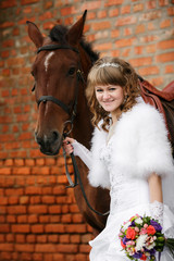 bride  in  wedding day against a brown horse and old brick wall
