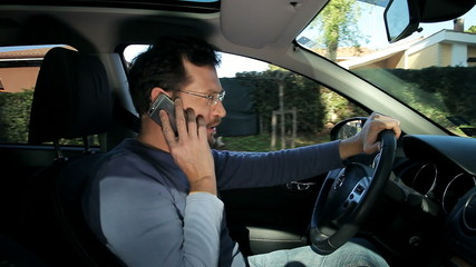 Man relaxed driving talking on the phone