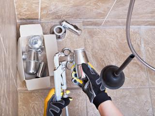 plumber repairs sink trap in bathroom