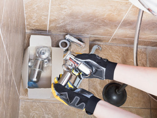 Sanitary technician replaces plumbing trap of sink