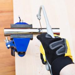sanitary technician saws metal trap pipe