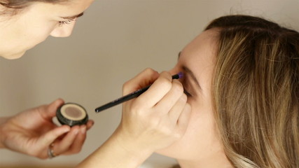 Beautician artist applying makeup to a model