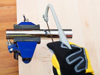 sanitary technician sawing plumbing drain pipe