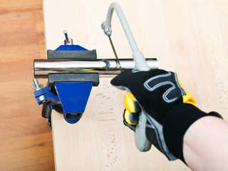 plumber saws metal trap pipe gripped in vice