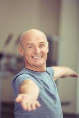 älterer mann im fitness-studio streckt die arme aus