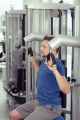 sportler trainiert seine arme an einem sportgerät