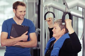 trainer betreut eine ältere frau im fitness-studio