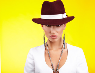 Fasionable woman in a hat over yellow background