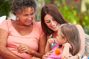 Grandmother,Mother And Granddaughter Sitting Outdoors