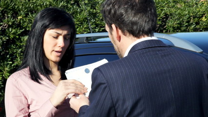 Salesman giving document and keys of new car