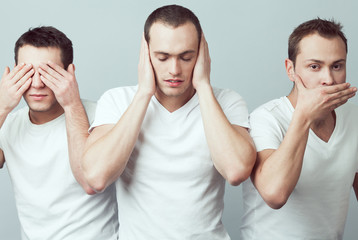 Closeup portrait of three young men in white t-shirts