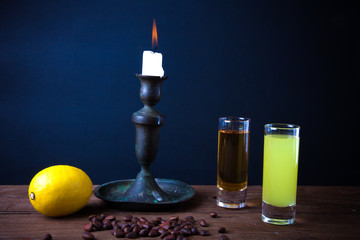 Two different drink on a wooden table with a candlestick. tinted