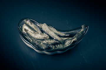 Canned fish pieces on oriental dish. Toned
