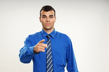 Young businessman in blue shirt shows on you