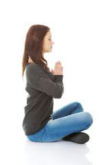 Pretty student girl meditating in lotus pose.