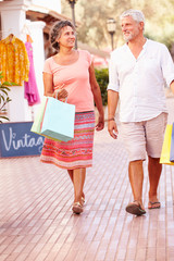 Mature Couple Walking Along Street With Shopping Bags