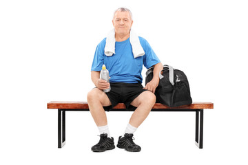 Mature man in sportswear sitting on bench