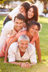 Multi Generation Family Lying In Pile Up On Grass Together