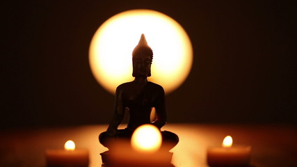 replica of Buddha statue and moving candle flames