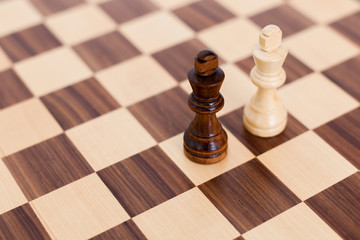 Two wooden chess pieces on a chess board