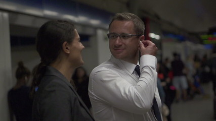 Happy businesspeople listening to music on metro station,