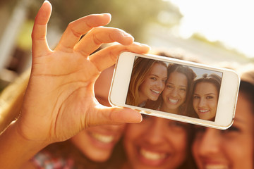 Female Friends On Holiday Taking Selfie With Mobile Phone