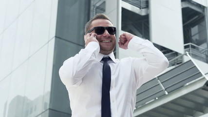 Successful, excited businessman with cellphone in the city,