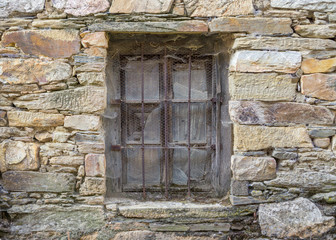 Old window with grille and stone wall