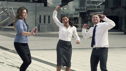 Happy businesspeople dancing in the city