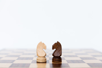 Two wooden horses chess pieces on a chess board