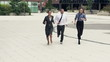 Happy businesspeople in hurry, running through pavement in city