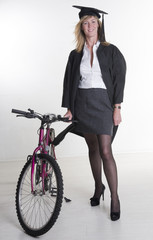 Mature university student in cap and gown with her bicycle
