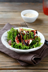 Light salad with figs, lettuce and balsamic sauce in a bowl