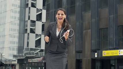 Happy businesswoman listening to music and dancing in the city