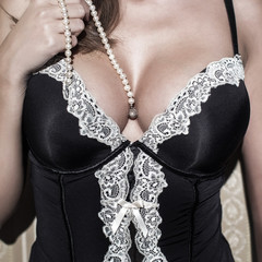 Sexy woman with big tits holding pearls