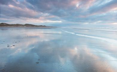 Spiegelend strand met wolkenlucht