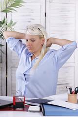Junge Frau streckt sich im Büro