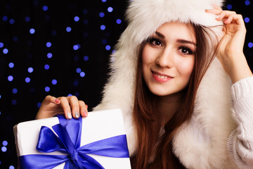 Beautiful girl holding gift box with blue ribbon