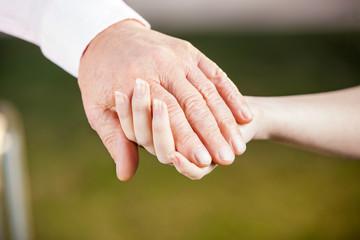 Nurse Holding Senior Man's Hand