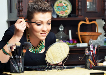 Beautiful elegant lady putting make up at home