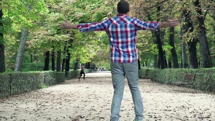 Happy man turning around in park during autumn