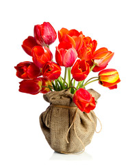 Beautiful bouquet of tulips in a vase made of sackcloth is